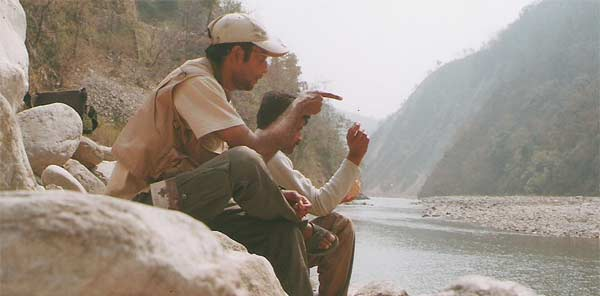 Expert Indian angler Vinay Badola sitting with local villager by the Kali river in Pancheshwar